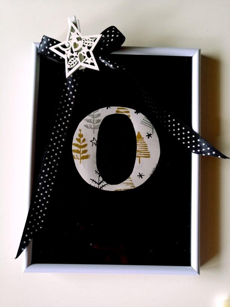 Slovo izrezano iz ukrasnog papira i stavljeno je na podlogu od crnog kolaža