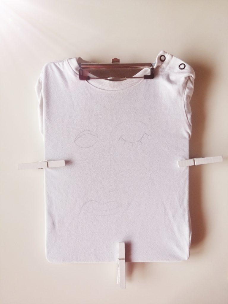 Majica učvršćena kvačicama i nacrtan uzorak za one line art